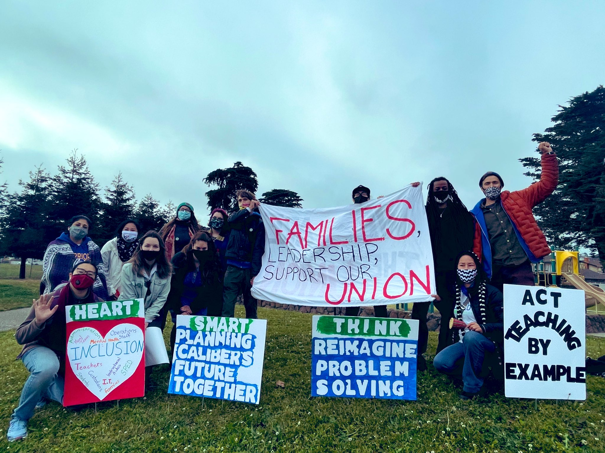 Members of the Caliber Workers Union gathered on grass holding a variety of signs and a banner in support of teachers and their union.