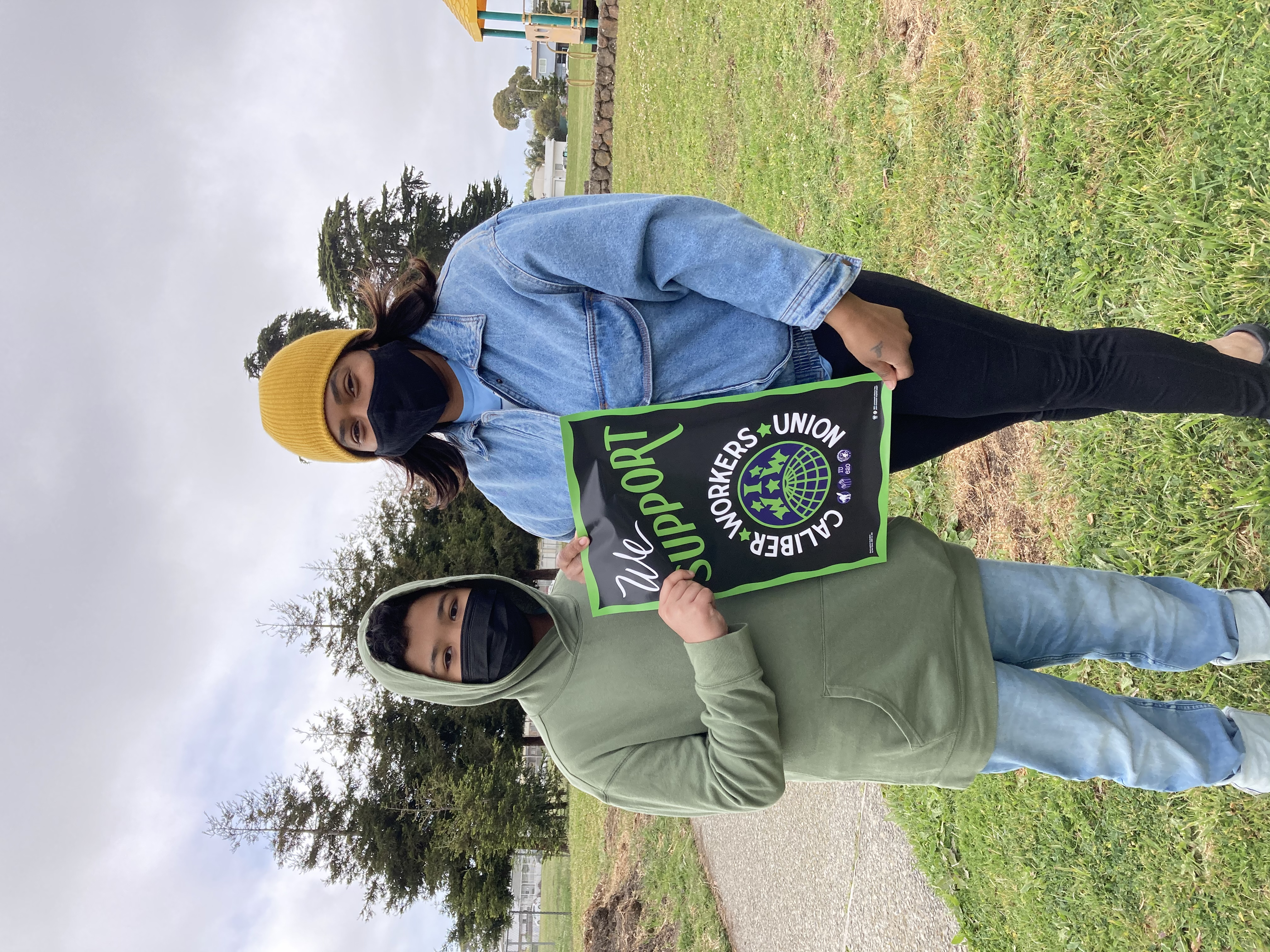 Two Caliber Workers Union members holding a sign in support of teachers and their union.